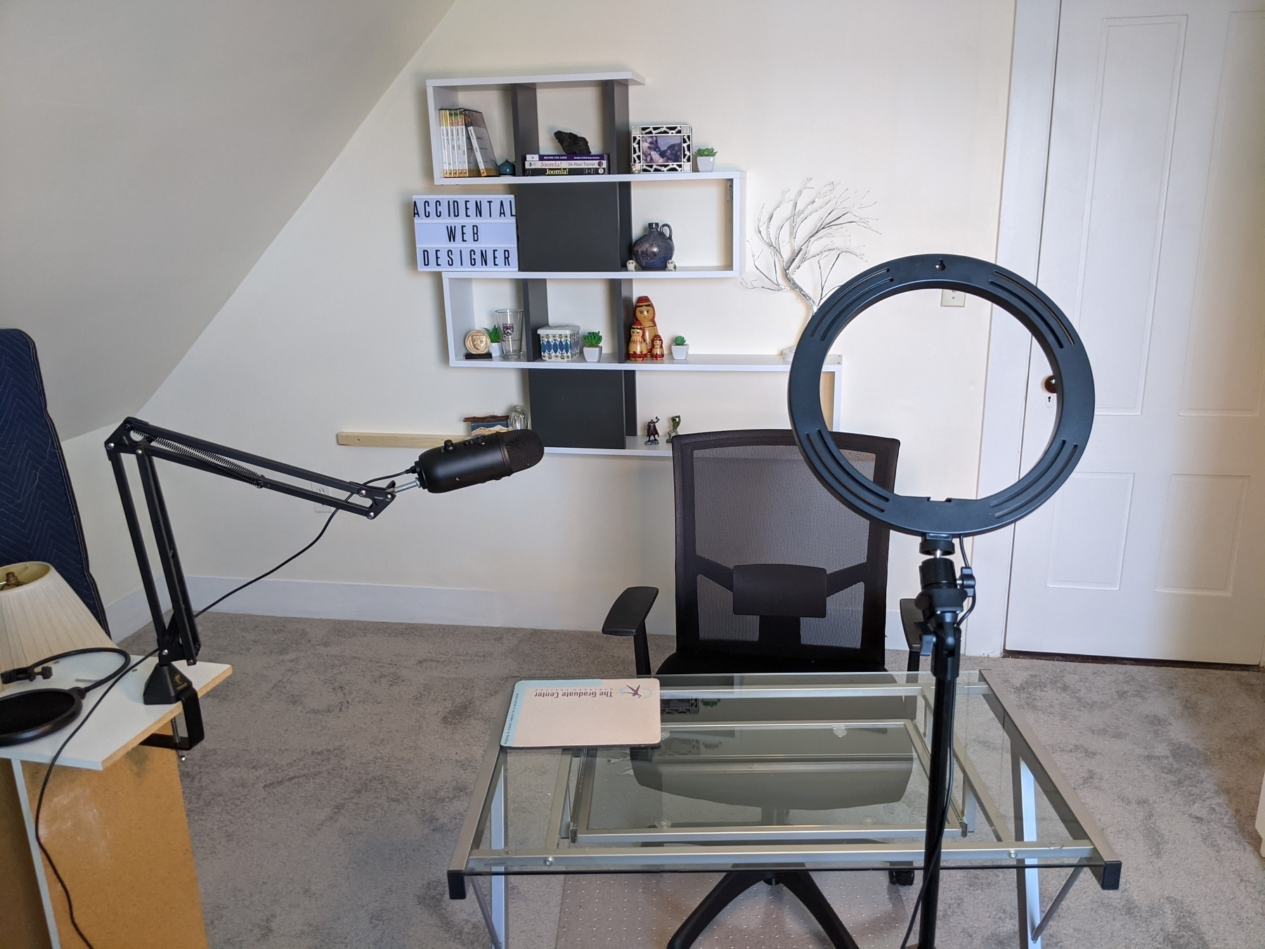 Photo of shelf on the wall, glass desk and chair, microphone on a boom.